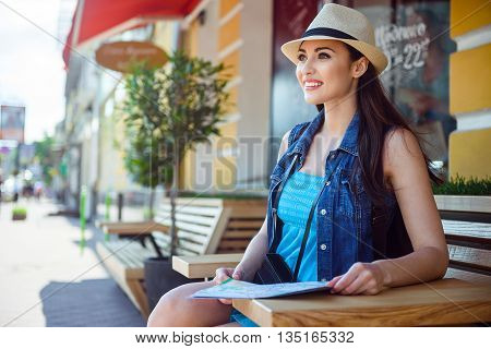 Happy female tourist is making her journey across city. She is sitting and resting. Woman is holding a map and smiling