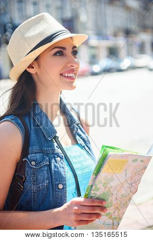 Beautiful young woman is walking in city with map. She is looking forward with interest and smiling