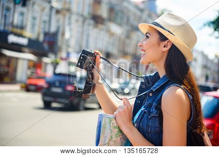 Happy female tourist is going sightseeing. She is photographing architecture and laughing. Girl is standing and holding a map