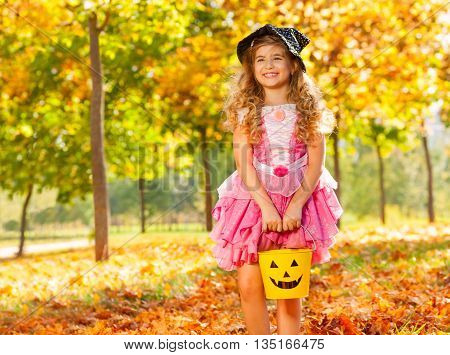 Girl in costume of princess hold small bucket standing alone in the forest during sunny autumn day time