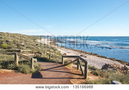 KALBARRI,WA,AUSTRALIA-APRIL 21,2015: People on the sandy beach on the Kalbarri Indian Ocean coast line with pathway and vegetated dunes under a clear blue sky.