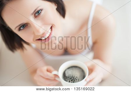 Relaxing with cup of coffee. Top view of beautiful young woman enjoying cup of coffee, looking at camera