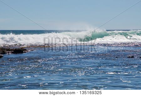Strong foamy Indian Ocean waves with beach reef at the Blue Holes beach under a blue sky in Kalbarri, Western Australia.