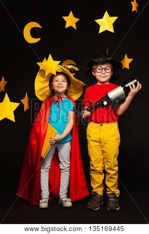 Full length photo of five years old boy and girl, playing sky watchers with a telescope, standing among handmade stars and moon