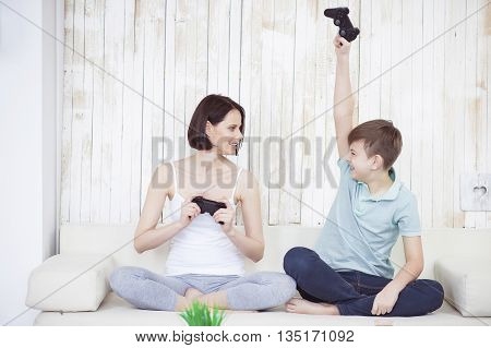 I won. Cheerful mother and her son playing video games together in living room