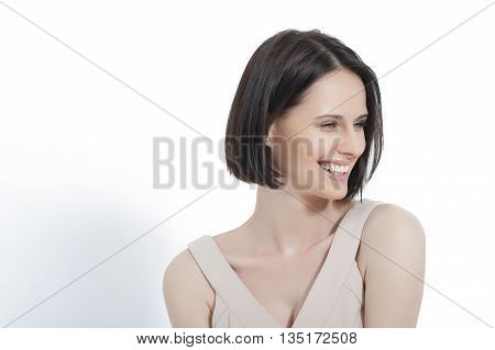 Beautiful laughter. Beautiful woman thinking happy looking up wearing cream dress, isolated on white background