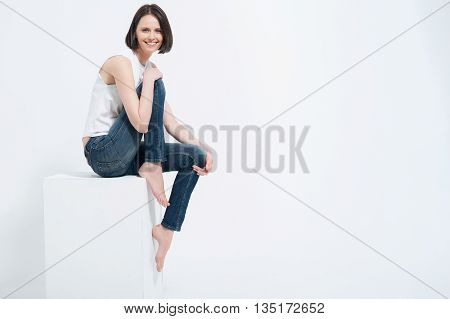 Stunning in any style. Portrait of beautiful lady wearing jeans and white top sitting on white cube posing, isolated on white background