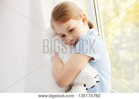 Lets be friends forever. Close up of cute little girl sitting on window and hugging her teddy bear
