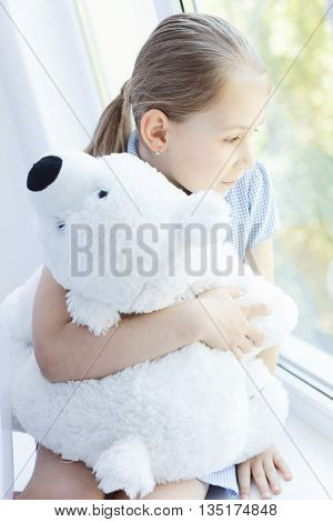 My best friend and me. Portrait of cute little girl hugging her teddy bear and looking at window