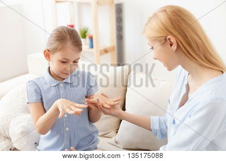 Happy loving family. Mother and daughter doing manicures and having fun, sitting on sofa in living room