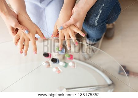 Inducing beauty together. Top view of mother and daughter having fun painting fingernails