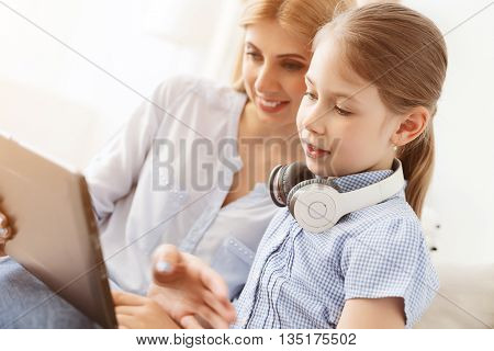 Technology has something for everyone. Young mother showing her daughter how to use digital tablet