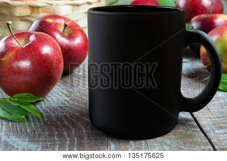 Black coffee mug mockup with apples. Empty mug mockup for product presentation. Coffee cup mockup.
