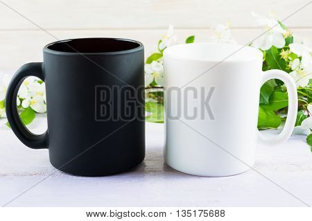 White and black mug mockup with apple blossom. Coffee cup mockup. Empty mug mockup for product presentation.