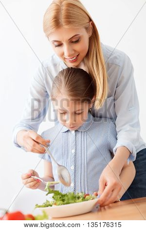 She loves making salads. Mother helping her daughter stirring salad on plate using spoon