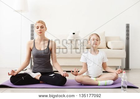 Working towards happy future. Mother and daughter doing yoga exercises on mat at home