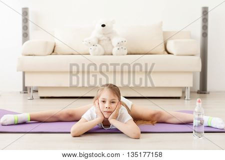 Stretch for success. Little girl lying on floor and doing stretching on sport mat
