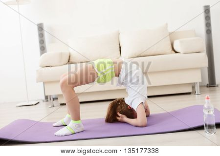 Balance and strength. Little cute little girl practicing yoga pose on mat at home