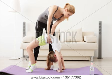Live healthy life. Mother and daughter doing yoga together at home