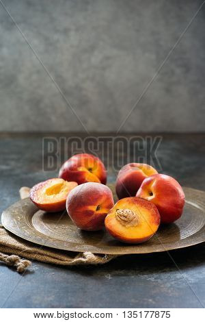 Peaches and nectarines on vintage tray over dark background selective focus