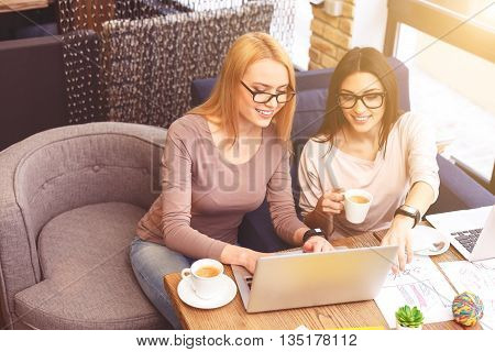Working together with joy. Pretty young woman is typing on laptop and laughing. Her friend is pointing finger at screen with inspiration. They are sitting and drinking coffee in cafe
