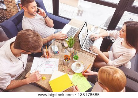 Top view of happy colleagues working in cooperation. They are sitting at table in cafe and smiling. Man is talking on mobile phone. Woman is using laptop