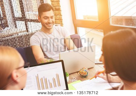 Smart young colleagues are working together with joy. They are using laptops and smiling
