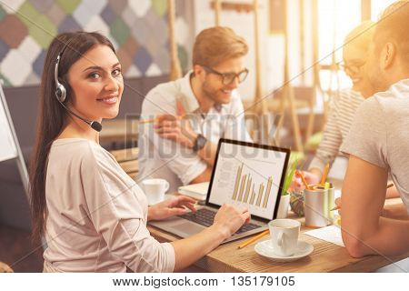 Pretty young woman is working on laptop and smiling. She is looking at camera while wearing headset. Her colleagues are talking and laughing on background