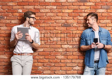 Joyful two men are using modern gadgets and smiling. They are standing and leaning on wall. Guy is holding a mobile phone. His friend is carrying tablet