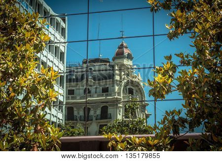 A beaux artes style building reflected in the glass of a modern building.