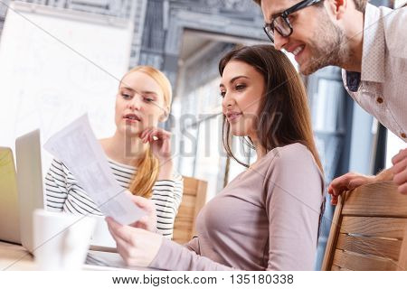 Clever young woman is explaining concepts of work to her colleagues. She is showing a document and smiling. Man is standing and smiling