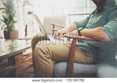 Bearded Businessman working Laptop modern Interior Design Loft Studio.Man sitting Vintage chair.Use contemporary Notebook, blurred background.Creative Process New Startup Ideas.Horizontal, film effect