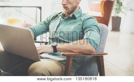 Bearded Businessman working Laptop modern Interior Design Loft Studio.Man chilling Vintage chair.Use contemporary Notebook, blurred background.Creative Process New Startup Ideas.Horizontal, film effect