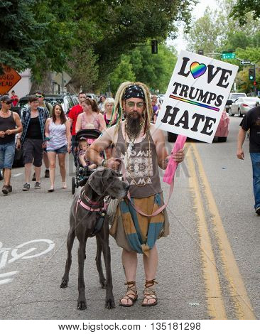 Boise, Idaho/usa - June 20, 2016: Man Walking With His Dog And A Sign Saying Love Trumps Hate During