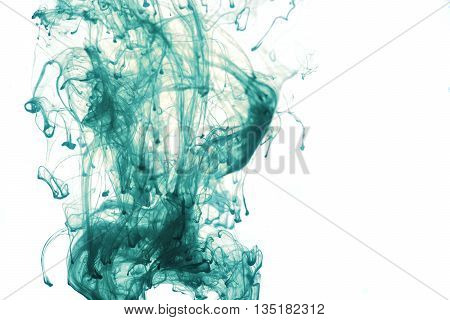 Blue ink dropped into water. Isolated on white background with a space for your text