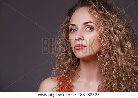 Closeup portrait of woman with curly hair. Looking at camera. Sensual portrait