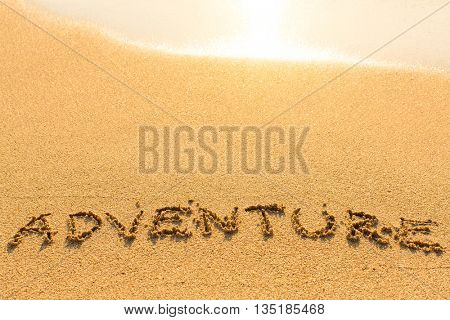 Adventure - word drawn on the sand beach with the soft wave.
