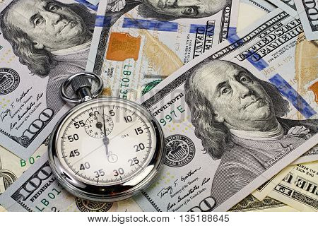 Stopwatch lays on pile of hundred dollar bills.