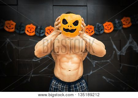 gym halloween theme gym halloween gourd bodybuilder with pumpkin near his head, a strong man squeezes a pumpkin, sportsman's trunk at the spider web and paper pumpkins background