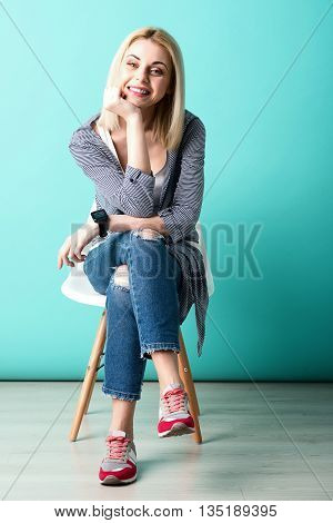 Portrait of beautiful blond girl having a seat and waiting. She is looking at camera with joy and smiling