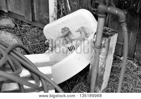 An old sink and other junk sitting out by a barn.