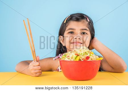 Happy Asian child eating delicious noodle, small indian girl eating noodles in red bowl with chopsticks, over blue background