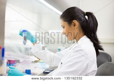 Closeup portrait scientist holding 50 mL conical tube with blue liquid solution laboratory experiments isolated lab background. Forensics genetics microbiology biochemistry