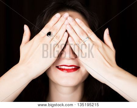 Close-up woman looks straight into the camera on a black background. laughing woman covering her eyes with her hand. expresses different emotions.