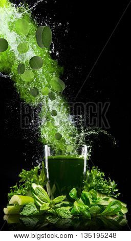 Healthy green vegetable smoothie isolated on black background.