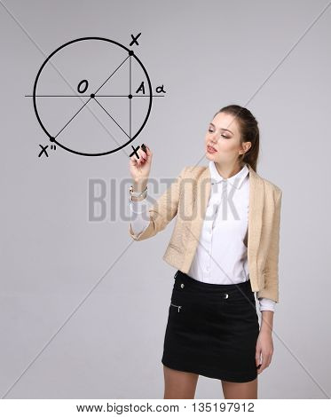 Woman with pen draws geometric shapes on grey background