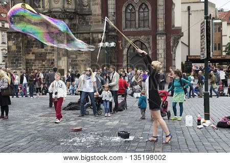 PRAGUE, CZECH REPUBLIC - JUNE 6, 2013: Street Artist of the Old Town Square in Prague blowing bubbles