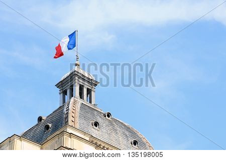 PARIS, FRANCE - JUNE 8, 2013:French flag on the dome of the Palais du Luxembourg in Paris against the sky