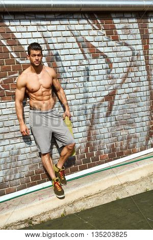 Full-length portrait of half-naked sporty man outdoor, leaning against wall, taking rest.