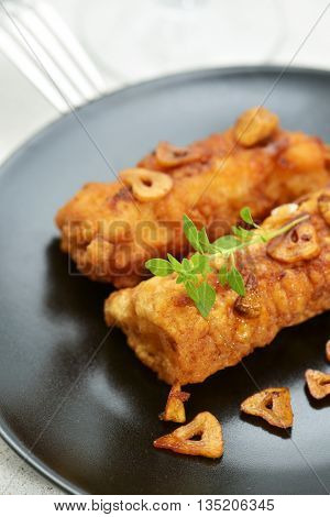 closeup of some battered and fried cod fillets covered with fried garlic served in a black plate